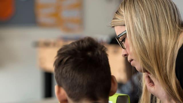 Eine blonde Frau mit Brille neben einem Schüler.