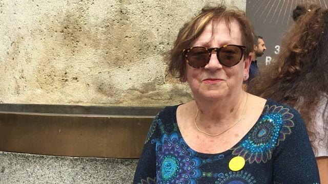 Amparo Grolimund auf der Puerta del Sol in Madrid. Sie hat kurze braun gefärbte Haare, trägt eine Sonnenbrille und eine blaue Blouse mit Blumensujets. Sie sitzt, man sieht nur ihren Oberkörper.