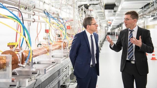 Zwei Männder diskutieren vor einer technischen Anlage.