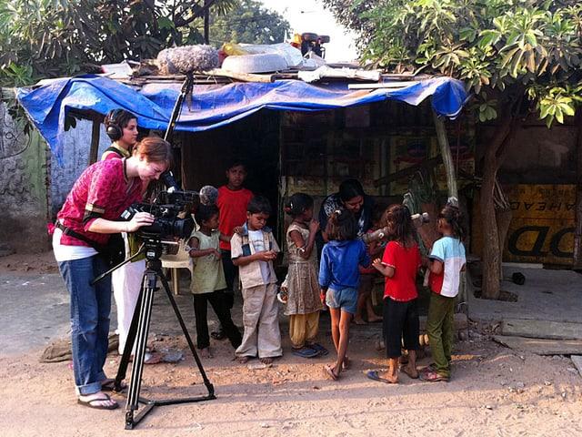 Eine Kamerfrau und eine Tontechnikerin vor einem Strassenstand mit Kindern davor.