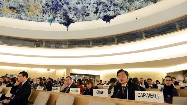Delegierte sitzen im Saal mit Länderschildern vor ihnen, auffällig die Decke mit farbig-künstlichen, herabhängenden Stalaktiten.