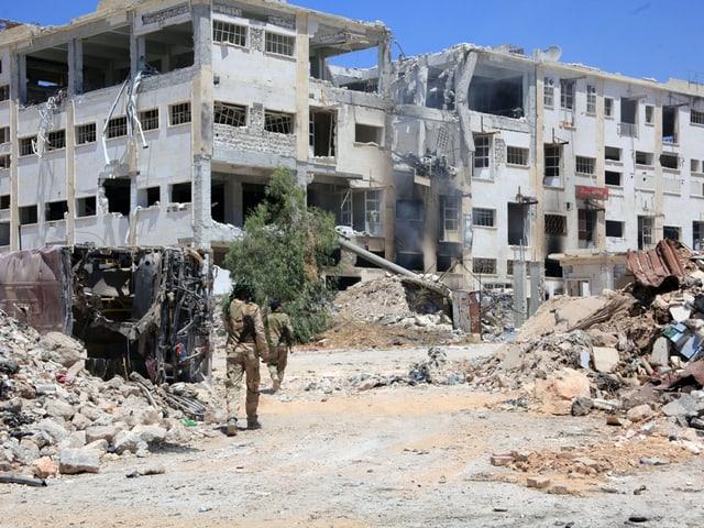 Zerbombte Häuser, davor bewaffnete Kämpfer in Tarnanzügen.