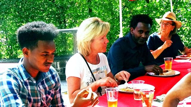 Eritreer und Schweizer beim gemeinsamen Essen.