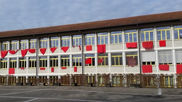Aus den Fenstern des Schulhauses Herzogenbuchsee hängen rote Tücher.