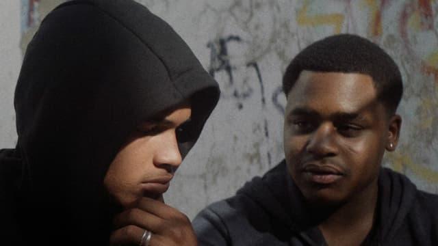 Zwei junge schwarze Männer, einer mit Hoodie.