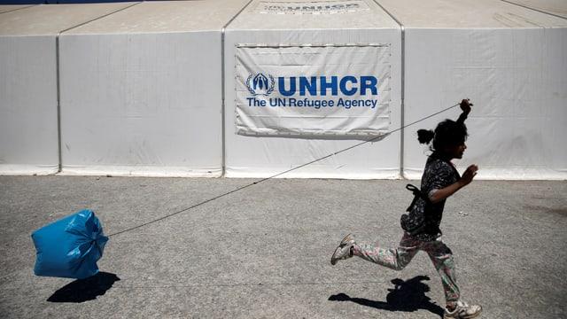 Mädchen rennt mit einem Platiksack an einer Schnur vor einem UNHCR-Zelt vorbei.