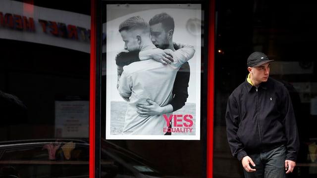 Zwei sich umarmende Männer auf einem Yes-Plakat. Daneben steht ein Mann, der wegschaut.