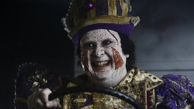Clown, weiss geschminkt, mit irrem Blick.