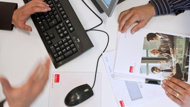 Tastatur und Maus, zwei Männer die gestikulieren, auf dem Pult diverse Adecco-Unterlagen.
