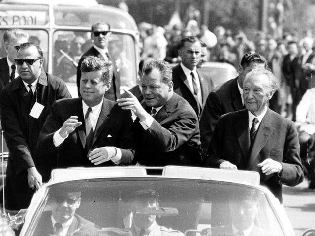 Berlins Bürgermeister Willy Brandt (mitte), der amerikanische Präsident J.F. Kennedy (links) und Bundeskanzler Konrad Adenauer (rechts) fahren in einem Cabriolet durch Berlin. (keystone)