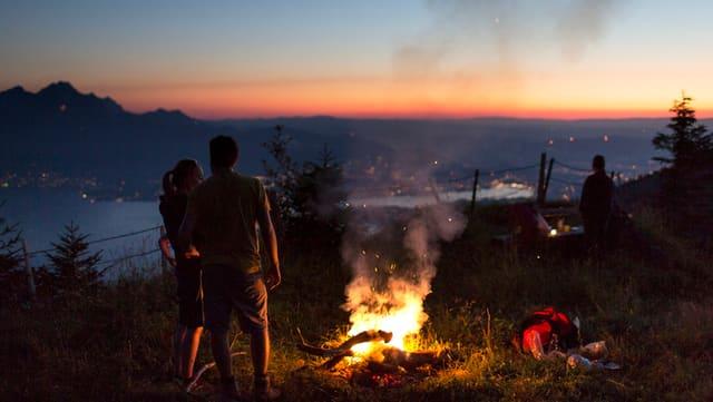 Ein Mann und eine Frau bei Sonnenuntergang an einer Feuerstelle auf der Rigi.
