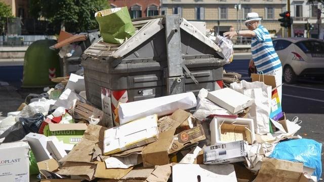 Ein Mann wirft eine Tüte auf einen Container, rundherum steht schon viel Abfall.