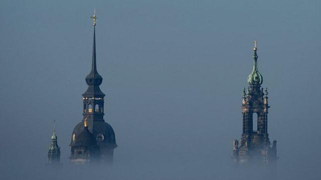 Zwei Kirchtürme, die aus dem Nebel ragen.