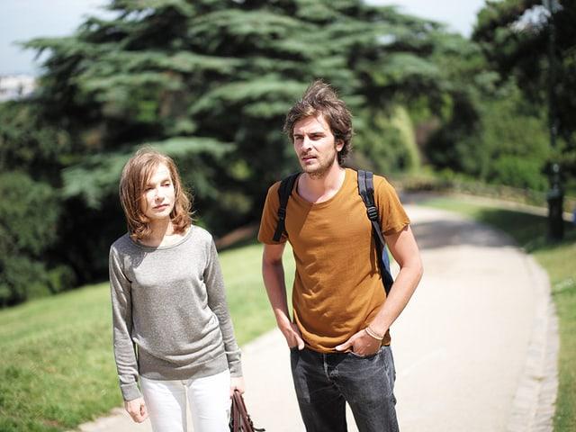 Eine Frau und ein jüngerer Mann laufen durch grüne Landschaft.