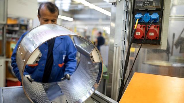 Mann in Arbeitskleidung, der Metallzylinder hält.