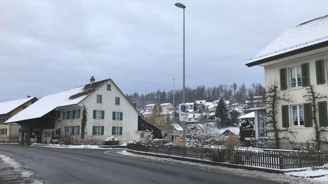 Blick auf die leere Dorfstrasse mit einigen Bauernhäusern