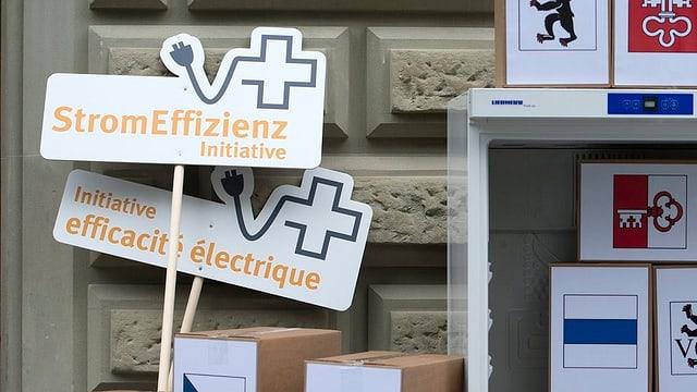 Schilder für die Stromeffizienzinitiative lehnen an eine Sandsteinwand.