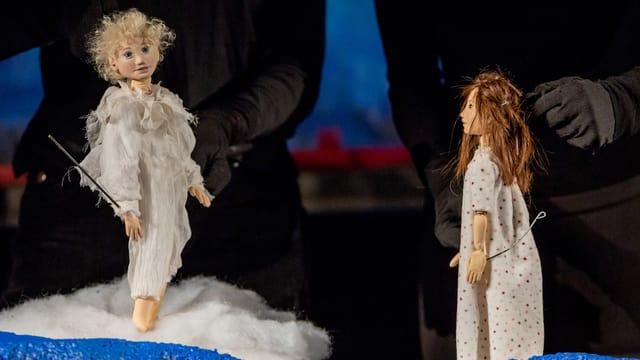 Zwei Puppenfiguren stehen auf einer Wolke aus Watte.