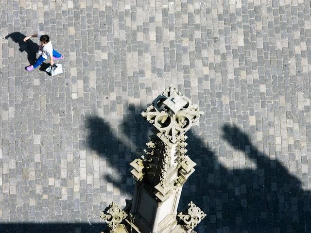 Blick von einer Kathedrale nach unten. Zu sehen ist ein kleines Türmchen der Kathedrale und eine Frau, sie über den Kirchplatz geht.