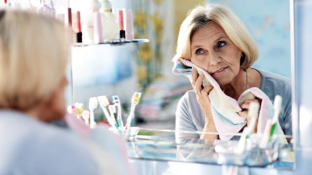 Ältere Frau studiert ihr Spiegelbild.