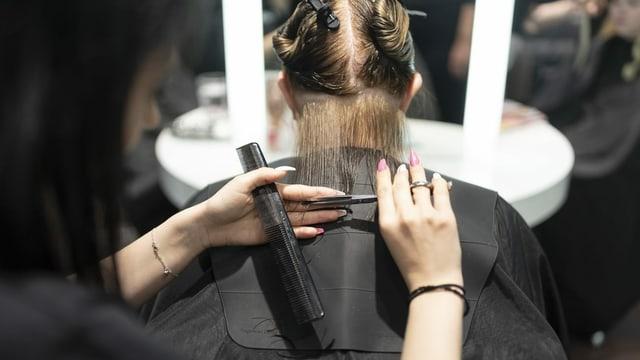Eine Coiffeuse schneidet einer Kundin die Haare