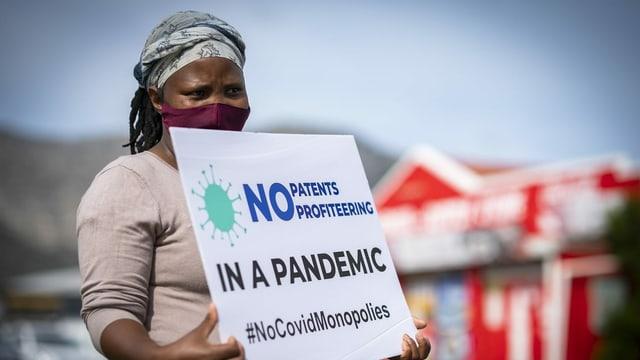 Frau mit Schild, Protest gegen Patente bei Impfstoffen