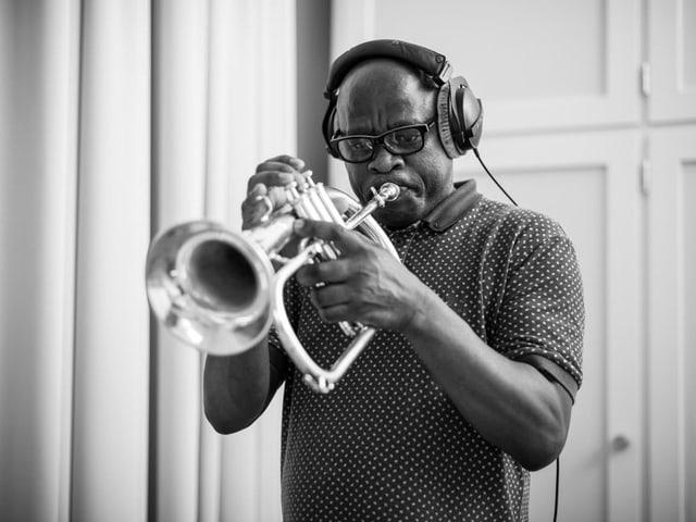 Feya Faku spielt Trompete und trägt einen Kopfhörer, halbnahe Aufnahme, s/w.
