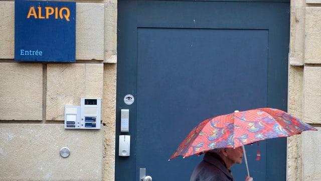 Ein Mann mit Regenschirm läuft an einem Hauseingang eines Alpiq-Gebäudes vorbei.