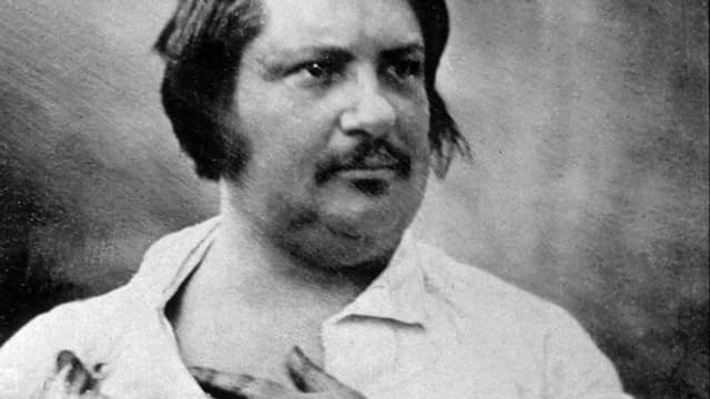 Porträt von Honoré de Balzac der eine Hand auf die Brust hält.