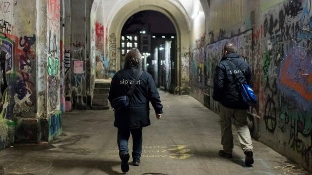 Zwei Menschen in Unterführung mit Graffiti an Wänden