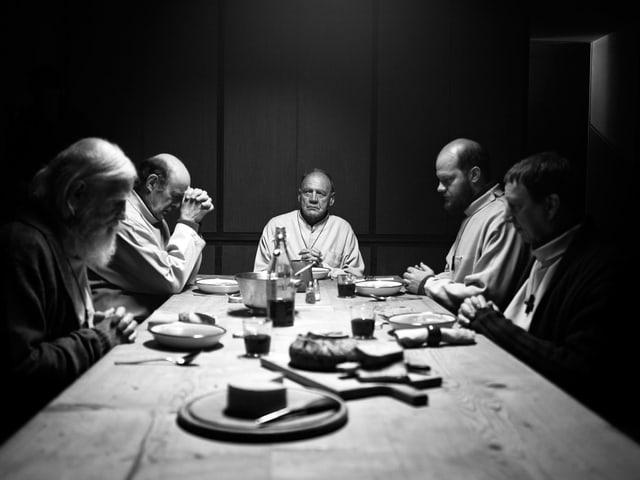 Fünf Mönche sitzen an einem Tisch