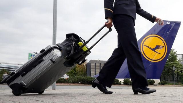 Eine Flugbegleiterin läuft vor einem Sitz der Lufthansa durch.