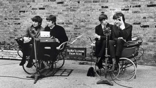 Vier Musiker sitzen auf zwei Kutschen auf einer Strasse.