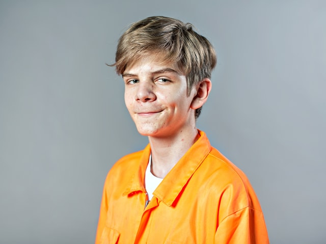 Teenager in orangefarbener Jacke.