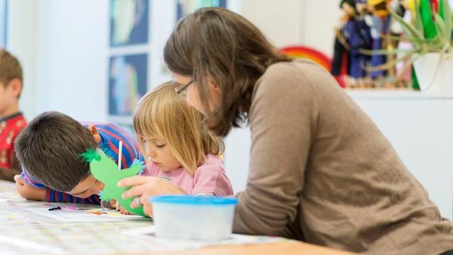 Ein Mädchen im Kindergarten bastelt, die Kindergartenlehrerin sitzt daneben und hilft.