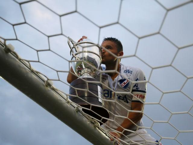 Nacionals Gonzalo Bergesio feiert mit der Trophäe auf dem Tor, nachdem sein Team die uruguayische Meisterschaft gewonnen hat.