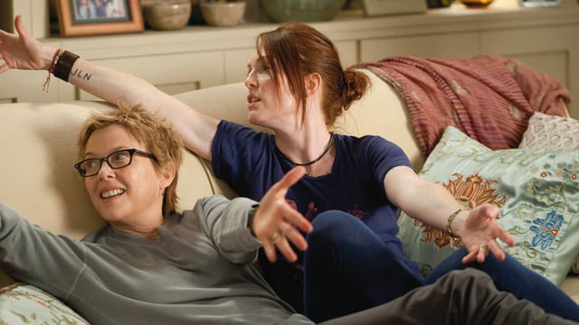 Zwei Frauen räkeln sich mit ausgebreiteten Armen auf einem Sofa.