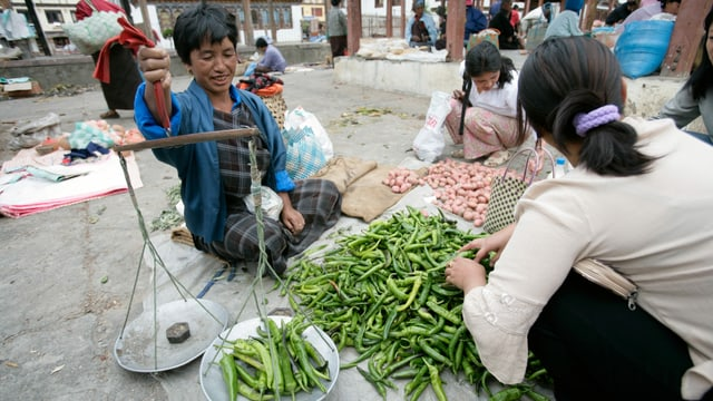 Auf einem Markt werden grüne Chilischoten gewogen.
