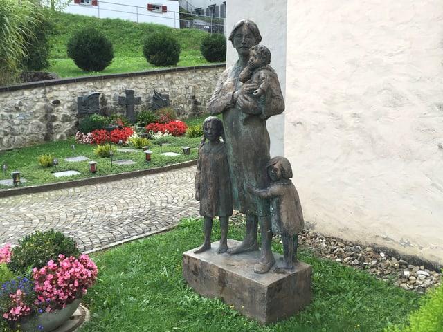 Metallskuptur von einer Frau mit drei Kindern.