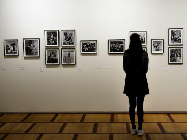 Eine Besucherin blickt auf Bischofs Fotografien aus den Anden.
