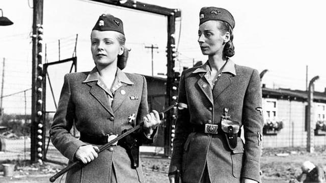 Zwei Frauen in Uniform stehen im KZ.