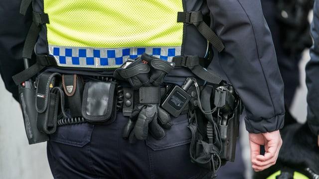 Purtret d'in policist ch'ins vesa ils accessoris da l'unifurma.