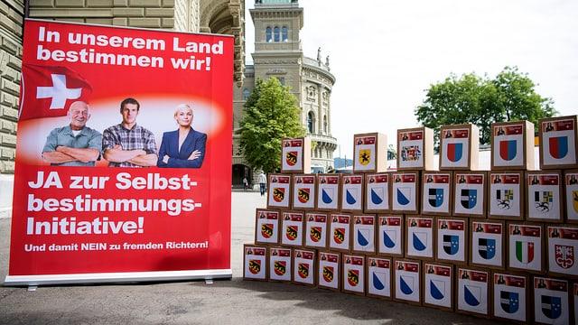 Kartonsschachachteln auf denen Kantonswappen aufgeklebt sind, Abstimmungsplakat.