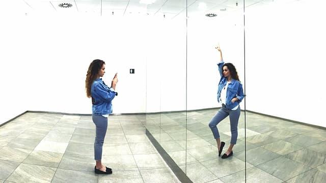 Eine Frau fotografiert sich im Spiegel. Durch eine Bildmontage macht ihr Spiegelbild eine andere Bewegung.