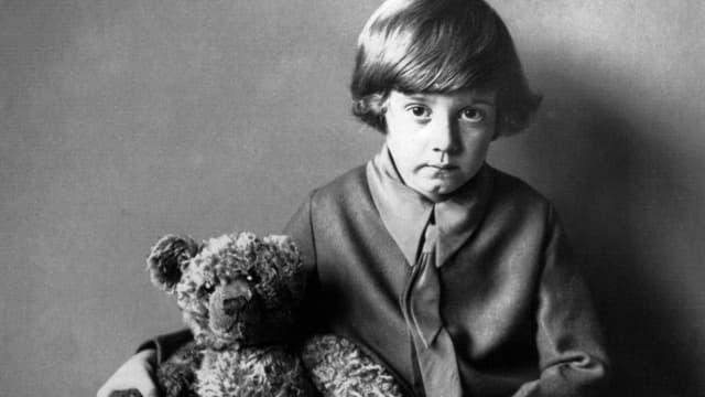 Ein junge schaut in die Kamera. Im Arm hält er einen Teddybären.