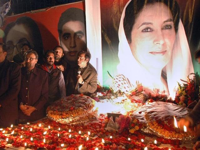 Bild von Benazir Bhutto neben trauernder Gemeinde am Jahrestag 2009.