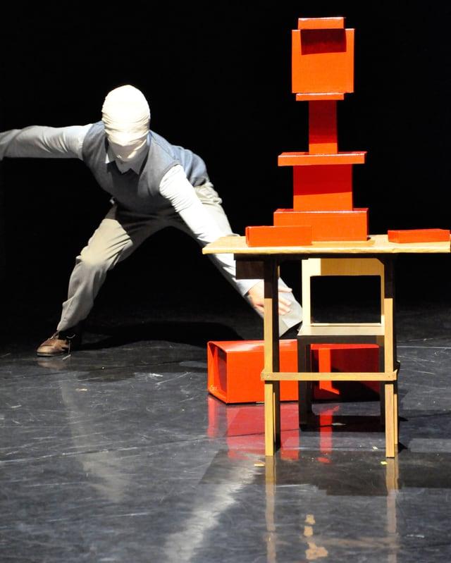 Ein Tänzer mit bandagiertem Gesicht vor einer Holzblockkonstruktion.