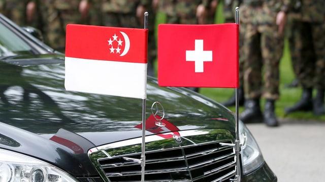 Zwei Flaggen auf einer Limousine angebracht.