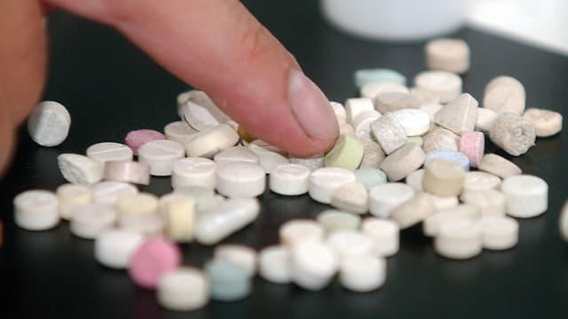 Symbolbild: Ein Finger wühlt in einem Haufen Pillen.