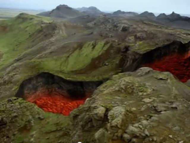 Eine gebirgslandschaft, in der sich ein rieisger Graben auftut, durch den Lava fliesst.